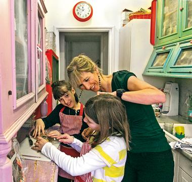 In foto: Costanza Miriano in cucina con le figlie più piccole.